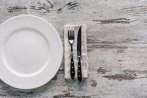 white plate and fork with knife on n