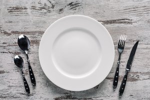 White plate and silverware on rustic