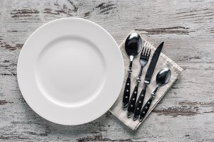 white plate and cutlery on napkin on