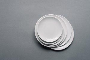 Stack of white porcelain plates on g