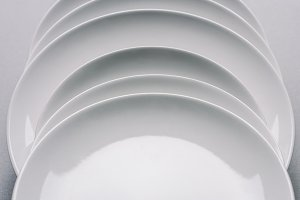 white plates in a row on white table
