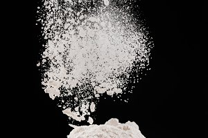flour falling from sieve on pile iso