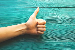 Woman's hand thumb up on wooden