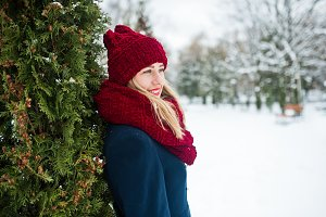 Blonde girl in red scarf and coat wa