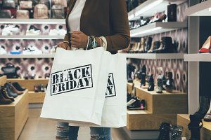 Female shopper holding shopping bags