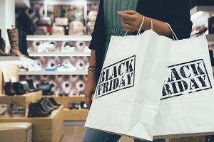 Female shopper holds shopping bags
