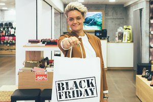 Smiling young woman holds shopping b