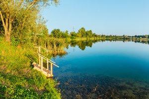 Summer lake calm beach with wood ste