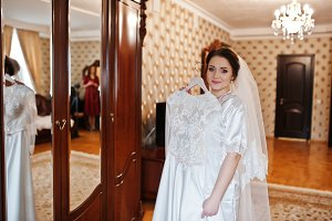 Cute brunette bride on silk robe wit