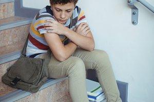 Sad schoolboy sitting alone