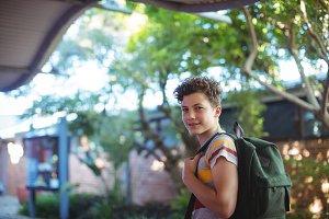 Happy schoolboy standing at campus