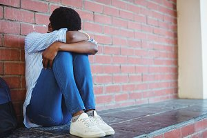 Sad schoolgirl sitting against wall