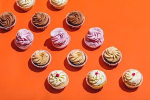 Colorful cupcakes in three rows on o