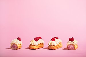 Four colorful eclairs with raspberri