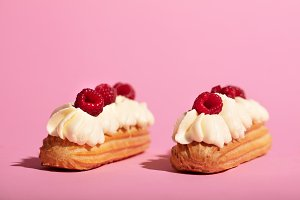 Two colorful eclairs laying on pink