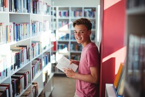Portrait of happy schoolboy reading
