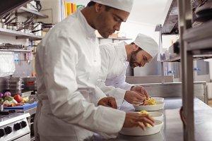 Two chefs garnishing food