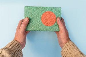 Hands giving green Christmas present