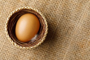 Chicken or hen egg in wicker basket