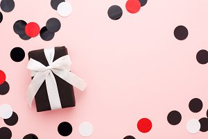 Black Gift box & confetti on pink.