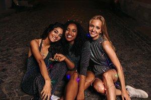 Happy friends sitting on sidewalk