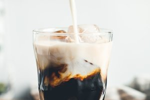 Pouring milk in a glass with coffee