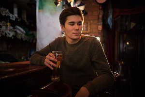 Young man drinking beer at the bar