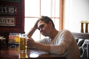 Stressed young man drinks beer in