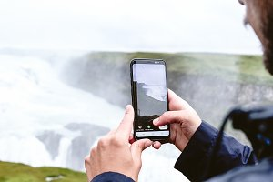 Boy instagramming a waterfall