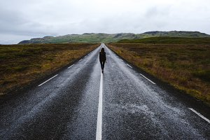 Girl walking away on an Iceland road