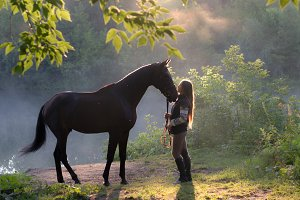 Young woman with her brown horse on