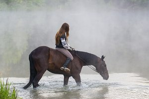 Young woman on a brown horse goes