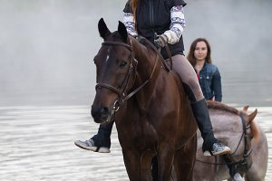 Two young women on horses goes out