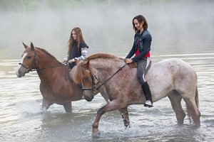 Two young women on horses stay in