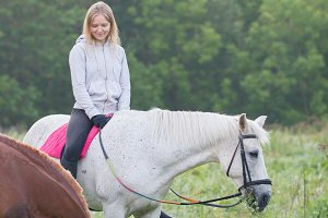 Pretty young woman on a white horse