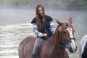 Young woman on a brown horse stays