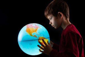 boy looking at earth globe close up