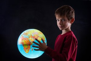 boy with a terrestrial globe looking