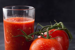 Fresh tomato juice in glass on stone