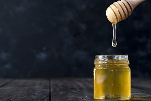 Honey dripping from dipper into jar