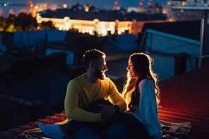 Loving couple is sitting on the roof