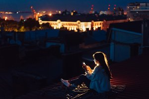 Young girl sits at night on the roof
