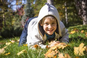 Happy little boy in the autumn park
