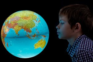 boy looking at glowing earth globe