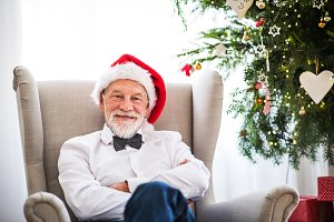 A senior man with a Santa hat at