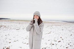 Gentle girl in gray coat and hat aga