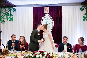 Wedding couple kissing at the table