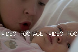 A boy kissing his baby sister on the