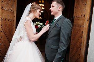 Beautiful bride pinning a buttonhole