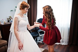 Good-looking bridesmaid helping brid